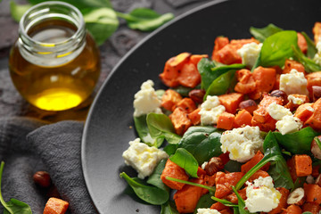 Healthy roasted sweet potato salad with spinach, feta cheese, hazelnut nuts in black plate, rustic background
