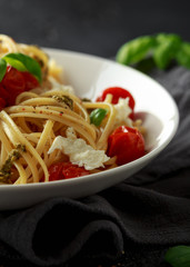 Pasta with green pesto sauce, roasted cherry tomatoes and mozzarella cheese in white plate on dark rustic background