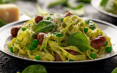 Homemade Pasta with green peas, spinach pesto and sausages. parmesan cheese. healthy food. close up