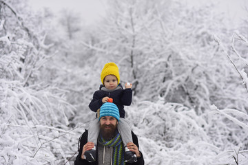 Snowballs. Game with father. Outdoor walk of happy father and son smiling. Young man and little boy, snowball in child hand and enjoying to winter walk together. December holidays. Merry Christmas