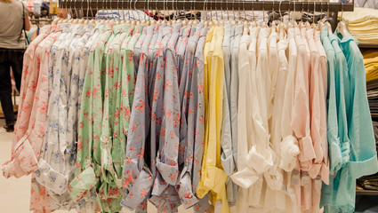 Colorful women's shirts on hangers in a retail shop. Fashion and shopping concept