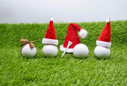 Merry Christmas to golfer with golf ball on green grass with Santa hat