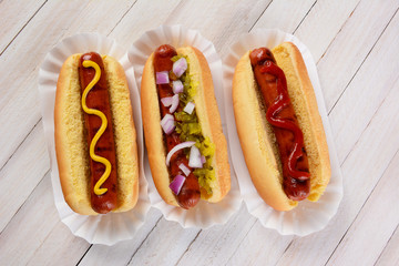 Three hot dogs on a wood table with different condiments