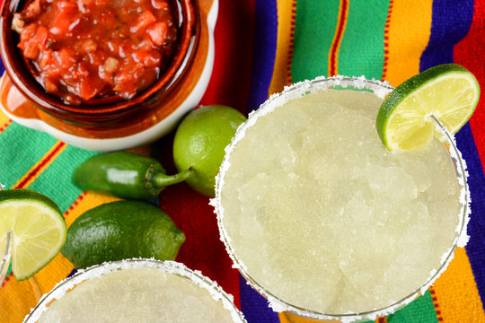 Margaritas and Salsa on a colorful  table cloth, with limes, and peppers.