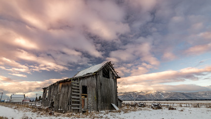 Farm barn in winter with morning colored clouds over it