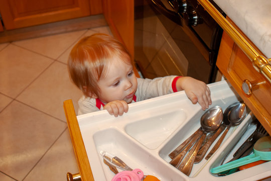 Baby is actively exploring the contents of kitchen box. Safety of the little explorer from unwanted objects and sharp corners, doors and drawers, to which, like a magnet, attracts the young know-all.