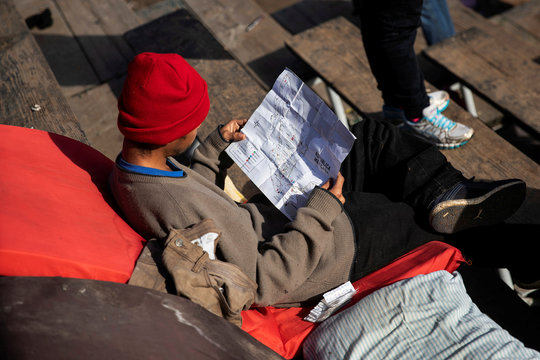 A migrant, part of a caravan of thousands from Central America trying to reach the United States, looks at a map of Mexico at a temporary shelter in Tijuana