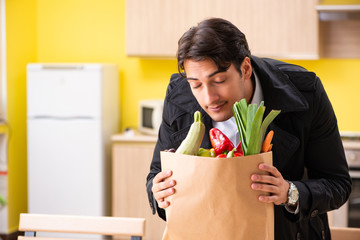 Young handsome man with vegetables in kitchen
