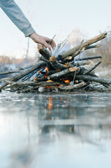 hand throwing firewood in the winter fire, folded on the ice