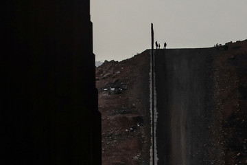 Migrant woman from Guatemala is silhouetted amid the border wall with her sons after illegally crossing into San Diego County from Tijuana, Mexico