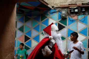 """Richard Gamboa, dressed up as Santa Claus, walks in an alley of the slum Cota 905 during the """"Santa en las calles"""" (Santa in the streets) event donating toys, food, and clothes in Caracas"""
