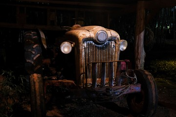 An operational antique or vintage tractor in an old dimly lit barn at nighttime.
