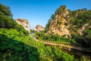 View of tourist walking on the bridge cross reservoir with mountain and blue sky background, Khao Ngu Stone Park, Ratchaburi, Thailand