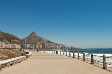 Mountains, hotels and deep blue water with waves at the Sea Point, beach promenade in Cape Town South Africa.