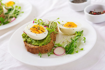 Healthy food. Breakfast. Avocado egg sandwich with whole grain bread on white wooden background.