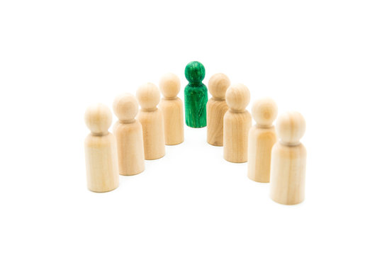 Green figure leading group of wooden figures in spearhead formation, isolated on white background