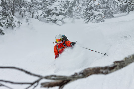Woman skier free rider goes down on powder snow in the mountains in a snowfall