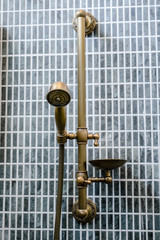 Wall-mount unlacquered brass rail and rain shower head, gray bathroom tile. Loft interior, minimalism concept, copy space