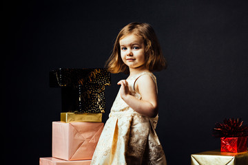 Portrait of a lovely little girl looking at camera surrounded with gifts, isolated on black studio background