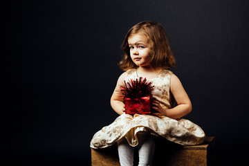 Portrait of a lovely little girl with red gift, isolated on black studio background