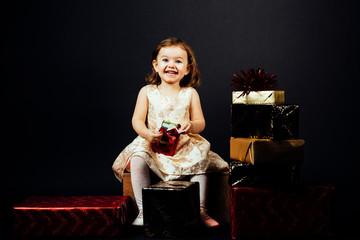 Portrait of a smiling  toddler girl holding a shiny red gift, isolated on black studio background