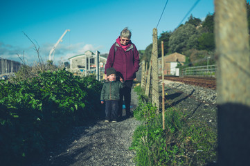 Toddler with grandmother walking by railway tracks