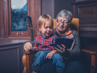 Toddler and grandmother looking at smartphone