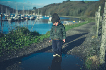 Little toddler walking in puddles by railway tracks