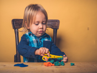 Little toddler playing with modeling clay