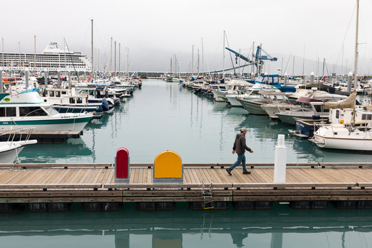 A man walks along the boardwalkd at the Seward small boat harbour with a large cruise ship in the background