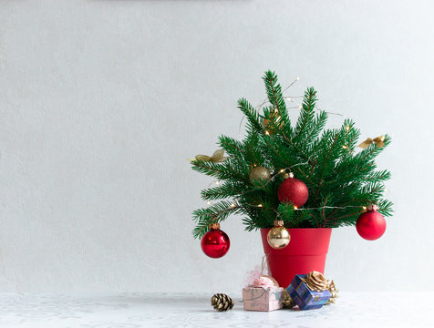 on a light background there is a Christmas decorated tree in a red pot under it