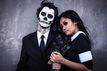 Skull face makeup guy and vampire gothic girl.