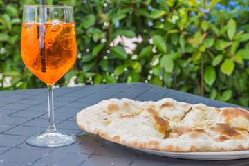 Wine glass of Aperol Spritz beside some Italian garlic pizza bread.