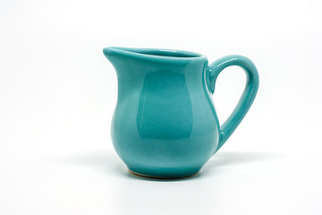 Green small ceramic pitcher on white background for utensil and dishware concept