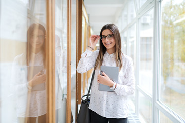 Happy Caucasian female student with eyeglasses standing next to noticeboard and holding tablet in hand. On shoulder bag.