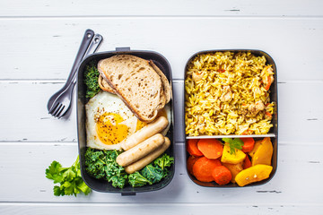 Meal prep containers with rice with chicken, baked vegetables, eggs, sausages and salad overhead shot. Wall mural