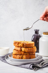 French toast with syrup on a gray plate.