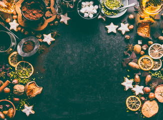 Christmas spices, chocolate and cookies background with ingredients for baking and sweet food: nuts, dried fruits, broken chocolate and spirits on dark background, top view with copy space for design