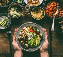 Female hands holding with healthy vegetarian bowl with various grilled vegetables, avocado and  chickpea hummus on rustic background, top view. Clean food and dieting nutrition concept