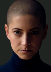 Portrait of a beautiful young woman with short hairstyle. Gorgeous female cancer patient portrait on dark background.