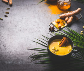 Black mug of vegan golden turmeric milk with spices on dark background with ingredients and palm leaves. Healthy hot drink. Immune boosting remedy , detox and dieting concept