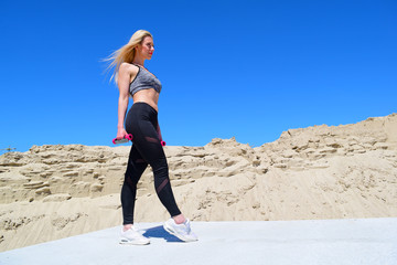 Young blonde girl with dumbbells standing in the desert in hot summer.
