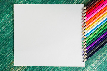 Mock up greeting card on the wooden background with colourful pencils for drawing.