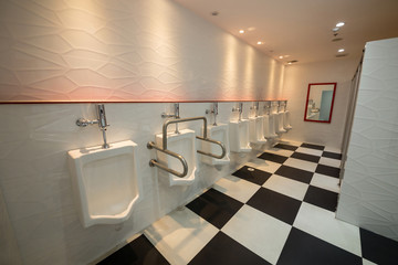 Row of white urinals in men's bathroom.