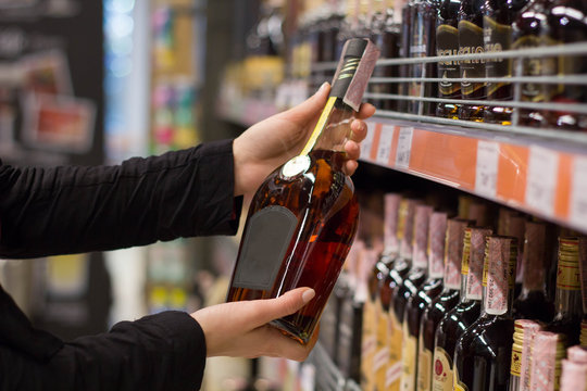 women's hands hold a bottle cognac