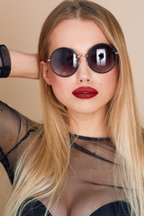 Pretty girl wear black glasses and pose to camera in yellow background studio