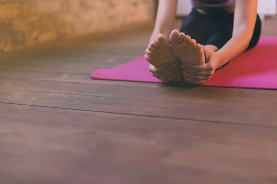 Close-up of a girl doing an asana bending forward with her hands towards her legs. Sitting on the floor on a  pink yoga mat.