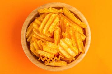 Crispy corrugated potato chips in wooden bowl