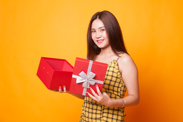 Young Asian woman open a golden gift box.