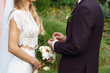 wedding couple wearing gold finger rings